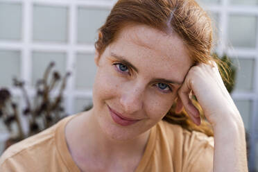 Portrait of smiling redheaded young woman with freckles - AFVF03958