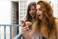 Portrait of two excited friends looking at smartphone - AFVF03961