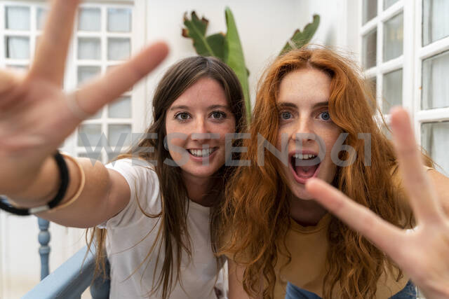 Portrait of two friends showing victory signs - AFVF03964 - VITTA GALLERY/Westend61