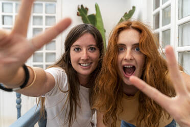 Portrait of two friends showing victory signs - AFVF03964
