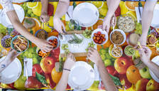 Healthy vegetarian meal on top of colorful table with friends, from above - AFVF03970
