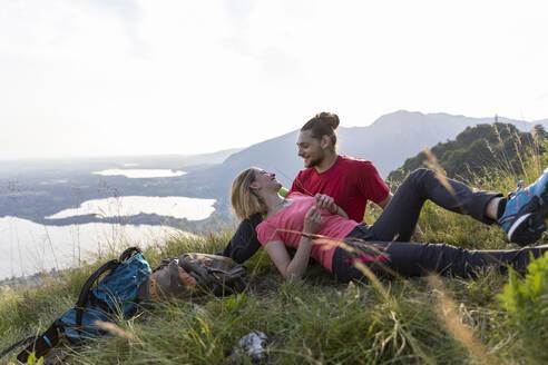 Hiking couple taking a break, lying in mountain meadow - MCVF00010