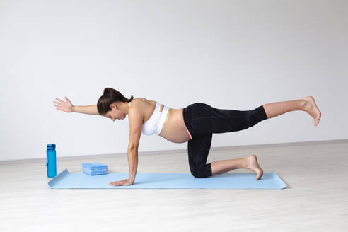 Young pregnant woman practicing yoga - HMEF00496