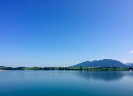 Scenic view of Forggensee lake against clear blue sky during sunny day at Ostallgaeu, Germany - JTF01329