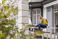 Relaxed woman sitting on terrace table in garden of her home - MJFKF00005