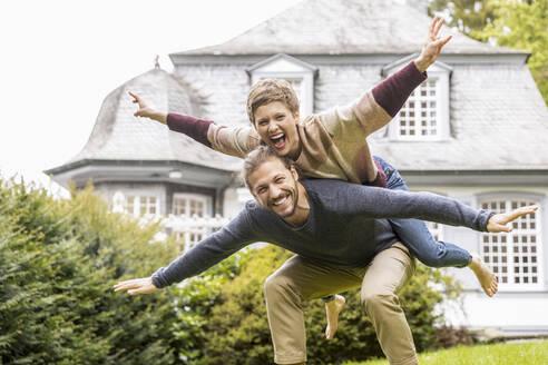Happy couple having fun in garden of their home - MJFKF00008