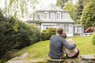 Rear view of couple sitting on a wall in garden - MJFKF00011