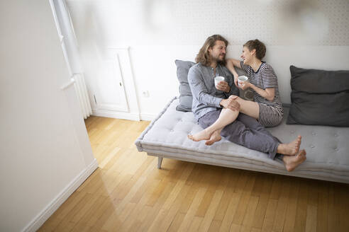 Happy young couple in pyjamas on bed couch at home - MJFKF00014