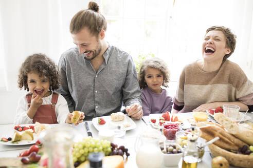 Happy family having lunch at home - MJFKF00023