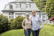 Happy senior couple standing in garden of their home - MJFKF00029