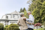Rear view of senior couple standing in garden of their home - MJFKF00032