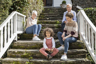 Senior couple with adult daughter and grandson sitting on stairs in garden of their home - MJFKF00038