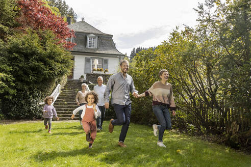 Happy extended family running in garden of their home - MJFKF00041