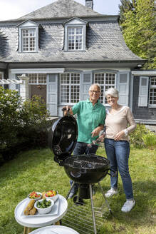 Happy senior couple having a barbecue in garden of their home - MJFKF00044