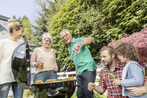 Extended family having a barbecue in garden - MJFKF00047