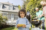 Portrait of boy with corn cob on a family barbecue in garden - MJFKF00050