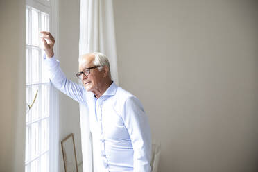 Senior man looking out of window at home - MJFKF00059