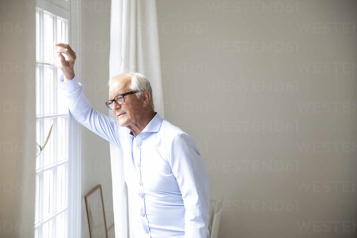 Senior man looking out of window at home - MJFKF00059 - MiJo/Westend61