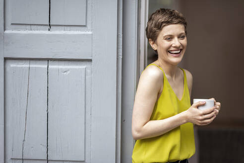 Laughing woman with cup of coffee at terrace door - MJFKF00065