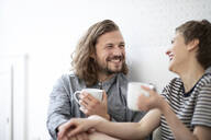 Happy young couple holding cups at home - MJFKF00071