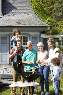 Happy extended family having a barbecue in garden - MJFKF00077