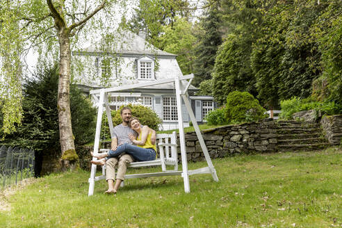 Relaxed couple in garden of their home - MJFKF00080