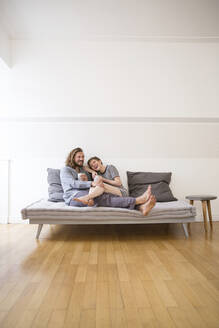 Happy young couple in pyjamas on bed couch at home - MJFKF00092