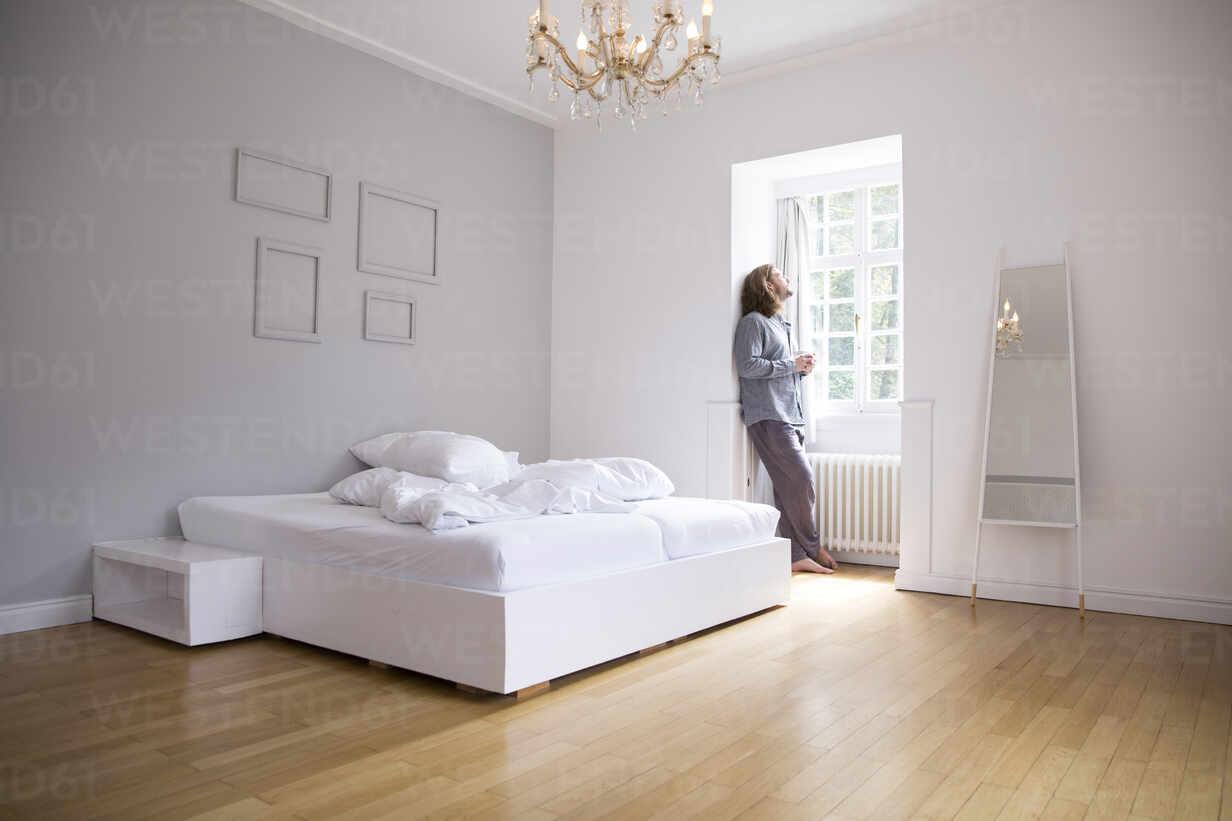 Young man in pyjama standing at the window in bedroom - MJFKF00101 - MiJo/Westend61