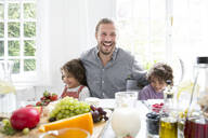 Happy father with two sons having lunch at home - MJFKF00107