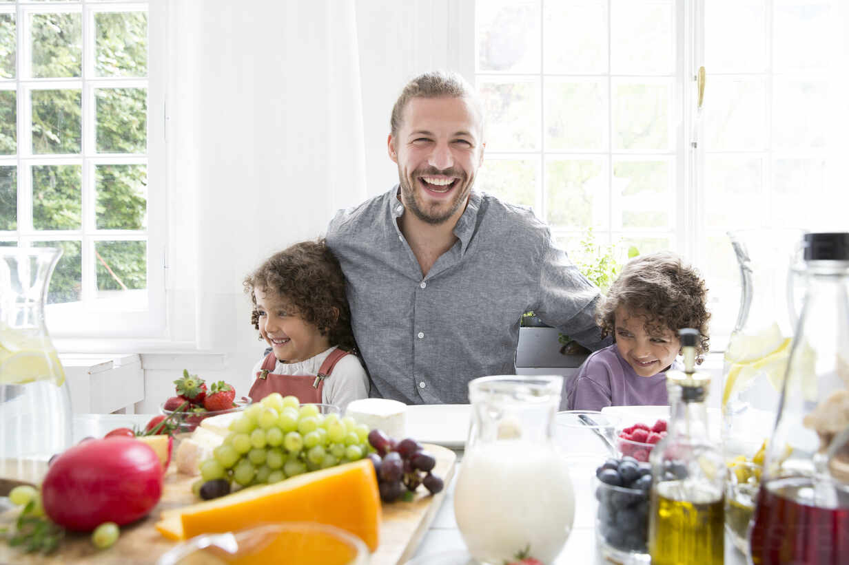 Happy father with two sons having lunch at home - MJFKF00107 - MiJo/Westend61