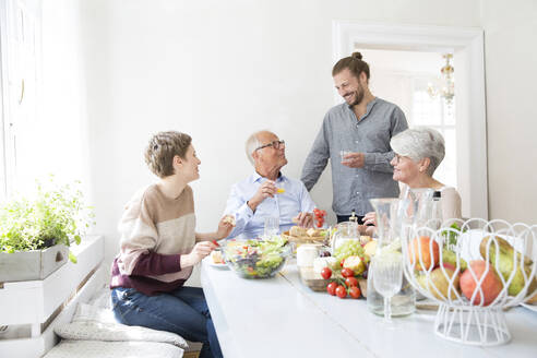 Happy senior couple with adult children having lunch at home - MJFKF00122