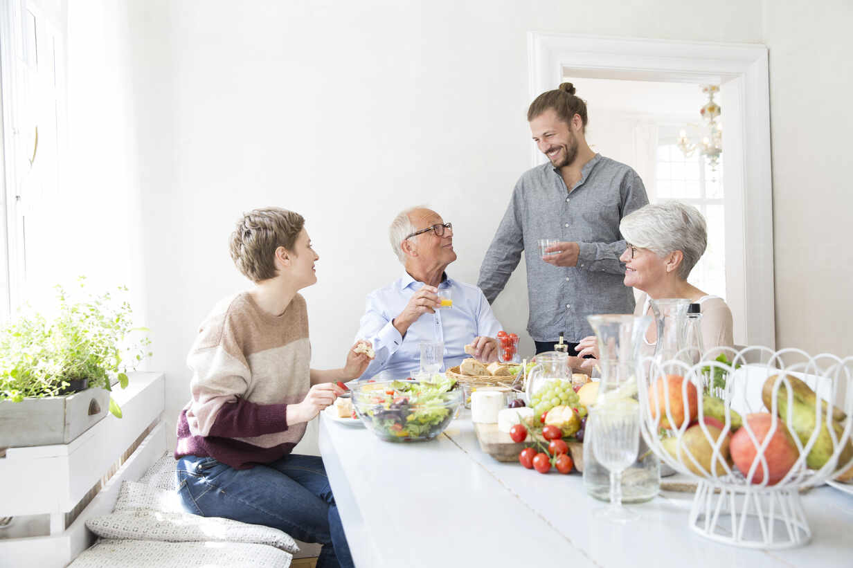 Happy senior couple with adult children having lunch at home - MJFKF00122 - MiJo/Westend61