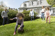 Happy extended family playing football in garden - MJFKF00134
