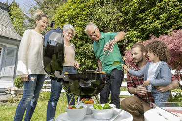 Extended family having a barbecue in garden - MJFKF00143