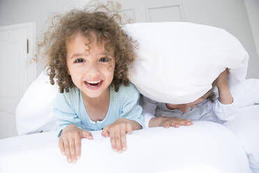 Portrait of happy boy with his brother in bed - MJFKF00161
