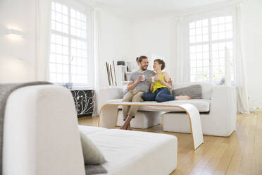 Happy young couple sitting on couch at home - MJFKF00170