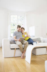 Happy young couple using tablet on couch at home - MJFKF00173