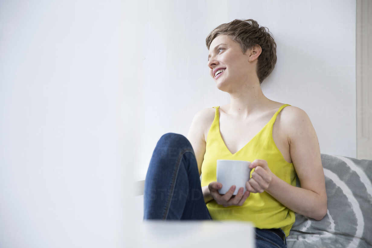 Smiling woman with cup of coffee at home - MJFKF00182 - MiJo/Westend61