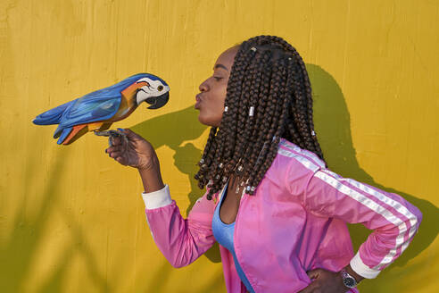 Woman kissing a wooden parrot on a yellow wall - VEGF00668
