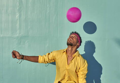 Young black man playing with a pink ball in front of a blue wall - VEGF00674