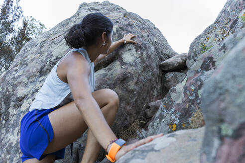 Young Asian woman climbing on a rock - JPTF00298