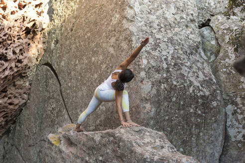 Young Asian woman practising yoga on a rock, triangle pose - JPTF00313