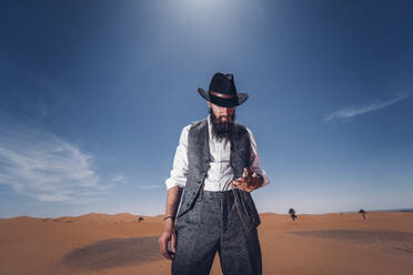 Man with a beard and hat in the dunes of the desert of Morocco checking the time - OCMF00713