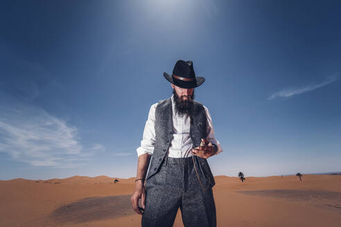 Classic man with a beard and hat on the dunes of the desert of Morocco. look at the clock - OCMF00713