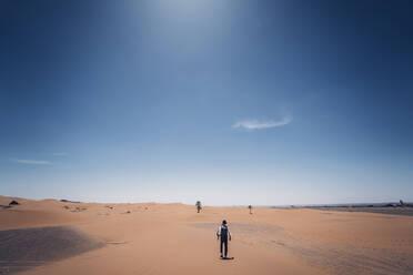 Lonely man with hat walking in the dunes of the desert of Morocco - OCMF00716