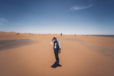 Man with a beard and hat in the dunes of the desert of Morocco - OCMF00719