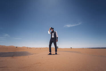Man with a beard and hat in the dunes of the desert of Morocco - OCMF00722