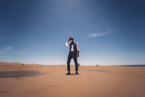 Classic man with a beard and hat walks on the dunes of the desert of Morocco. - OCMF00722