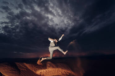 Man with a beard and hat jumping in the dunes of the desert of Morocco at dusk - OCMF00725