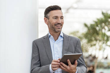 Smiling businessman with tablet in the city - DIGF08417